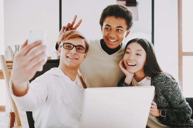 Jeune créateur souriant faisant selfie avec des collègues