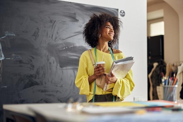Jeune créatrice de mode afro-américaine positive avec ruban à mesurer, tasse et papiers