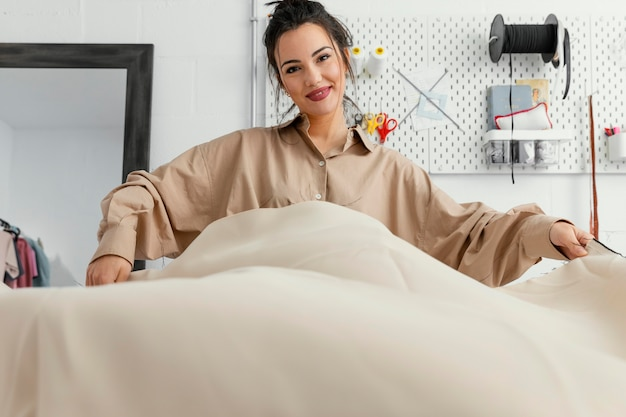 Jeune créatrice de mode travaillant seule dans son atelier