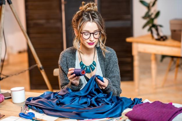 Jeune créatrice de mode travaillant avec un tissu bleu assis dans le beau bureau avec différents outils de couture sur la table
