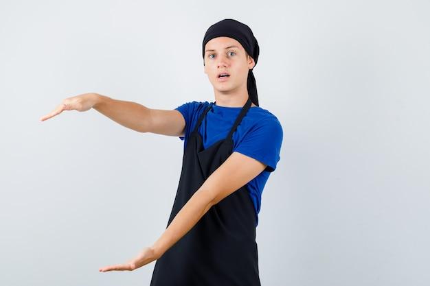 Jeune cuisinier adolescent montrant un signe de grande taille en t-shirt, tablier et l'air perplexe, vue de face.