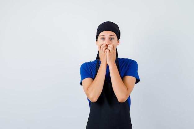 Jeune cuisinier adolescent en t-shirt, tablier avec les mains sur la bouche et l'air terrifié, vue de face.