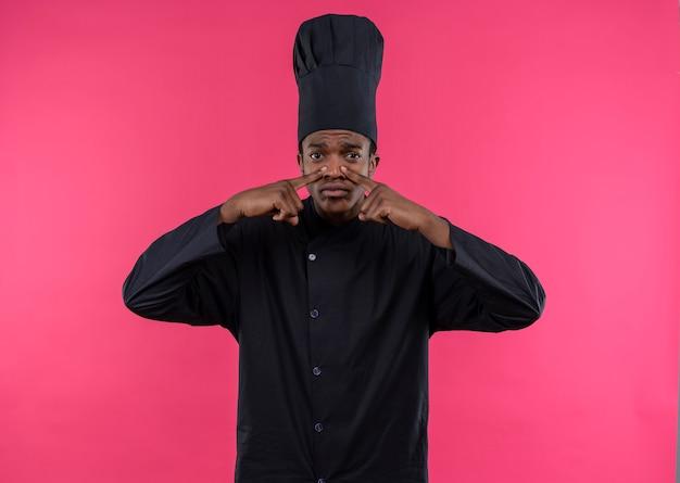 Jeune cuisinier afro-américain agacé en uniforme de chef ferme le nez avec les doigts des deux mains isolé sur fond rose avec copie espace
