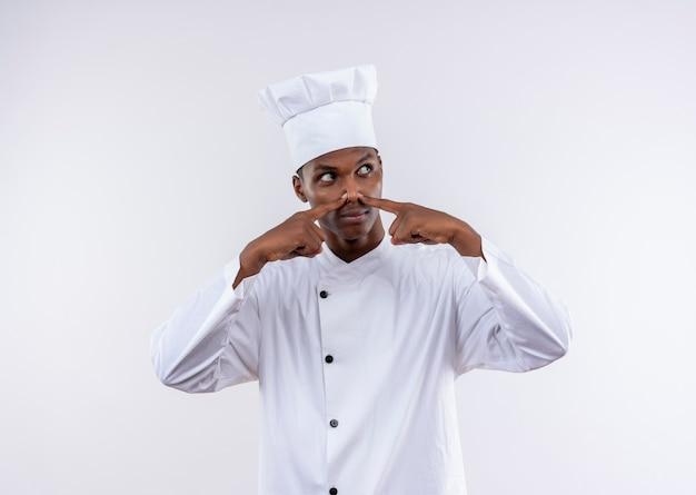 Jeune cuisinier afro-américain agacé en uniforme de chef ferme le nez isolé sur fond blanc avec copie espace