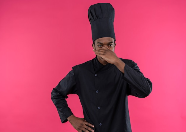 Jeune cuisinier afro-américain agacé en uniforme de chef tient le nez et met la main sur la taille isolé sur fond rose avec copie espace