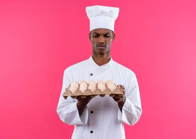 Jeune cuisinier afro-américain agacé en uniforme de chef tient et regarde lot d'oeufs frais isolé sur fond rose avec copie espace
