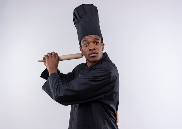 Jeune cuisinier afro-américain agacé en uniforme de chef tient le rouleau à pâtisserie avec les deux mains isolé sur fond blanc avec copie espace