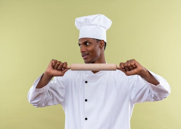 Jeune cuisinier afro-américain agacé en uniforme de chef tient le rouleau à pâtisserie droit avec les deux mains et regarde sur le côté isolé sur fond vert avec espace de copie