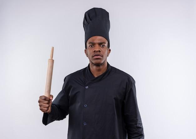 Jeune cuisinier afro-américain agacé en uniforme de chef tient le rouleau à pâtisserie isolé sur fond blanc avec copie espace
