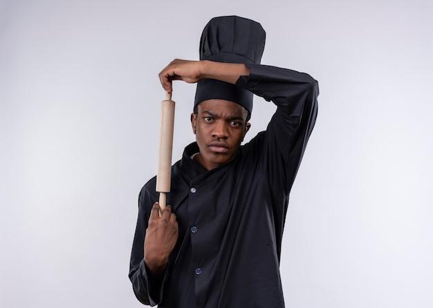 Jeune cuisinier afro-américain agacé en uniforme de chef tient le rouleau à pâtisserie tout droit isolé sur fond blanc avec copie espace