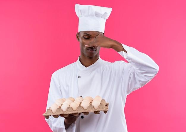 Jeune cuisinier afro-américain annpyed en uniforme de chef détient lot d'oeufs frais et ferme le nez avec la main isolé sur fond rose avec copie espace