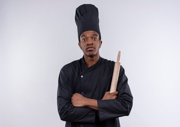 Jeune cuisinier afro-américain confiant en uniforme de chef croise les bras et tient le rouleau à pâtisserie isolé sur fond blanc avec copie espace