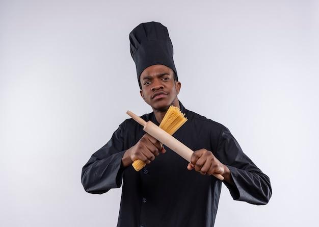 Jeune cuisinier afro-américain confiant en uniforme de chef détient bouquet de spaghettis et rouleau à pâtisserie isolé sur fond blanc avec copie espace