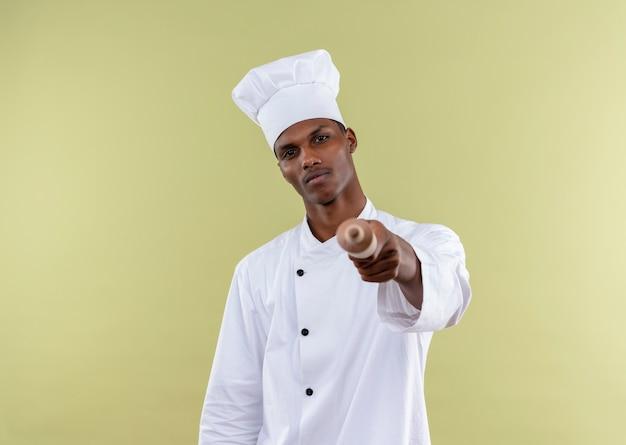 Jeune cuisinier afro-américain confiant en uniforme de chef détient la broche rooling isolé sur fond vert avec copie espace