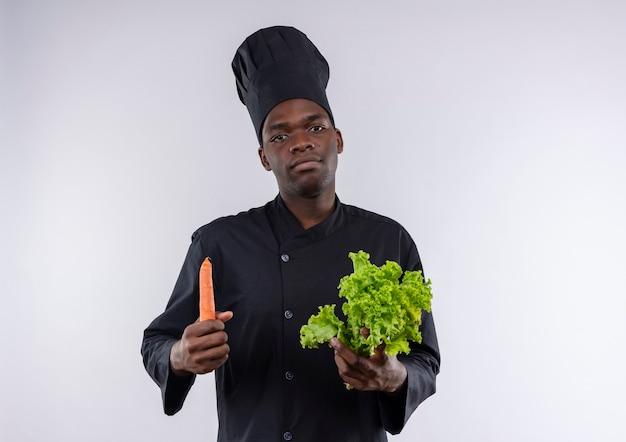 Jeune cuisinier afro-américain confiant en uniforme de chef détient la salade et la carotte sur blanc avec copie espace