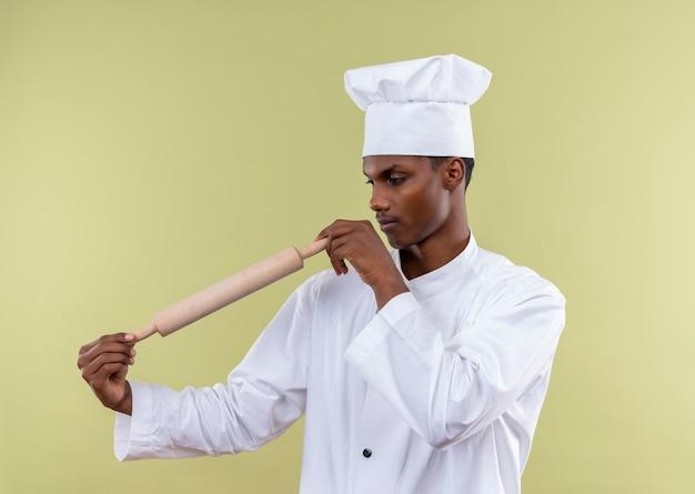 Jeune cuisinier afro-américain confiant en uniforme de chef tient et regarde le rouleau à pâtisserie isolé sur fond vert avec espace de copie