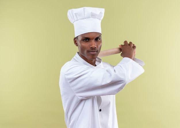 Jeune cuisinier afro-américain confiant en uniforme de chef tient le rouleau à pâtisserie derrière avec les deux mains isolé sur fond vert avec copie espace