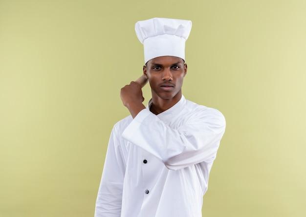 Jeune cuisinier afro-américain confiant en uniforme de chef tient le rouleau à pâtisserie derrière avec la main isolé sur fond vert avec copie espace