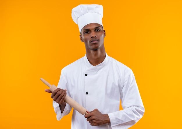 Jeune cuisinier afro-américain confiant en uniforme de chef tient le rouleau à pâtisserie avec les deux mains isolé sur fond orange avec copie espace