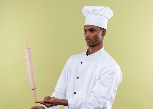Jeune cuisinier afro-américain confiant en uniforme de chef tient le rouleau à pâtisserie directement sur le doigt isolé sur fond vert avec copie espace