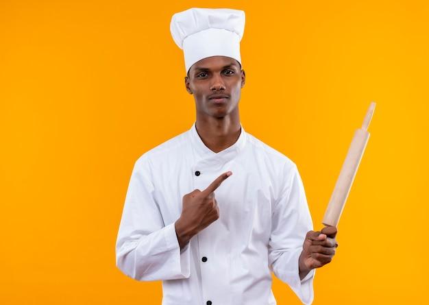 Jeune cuisinier afro-américain confiant en uniforme de chef tient le rouleau à pâtisserie et les points à la broche isolé sur fond orange avec copie espace