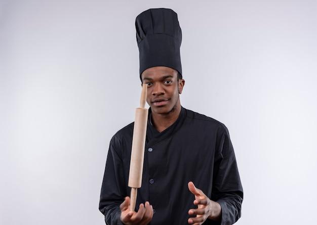 Jeune cuisinier afro-américain confiant en uniforme de chef tient le rouleau à pâtisserie tout droit sur le doigt isolé sur fond blanc avec copie espace
