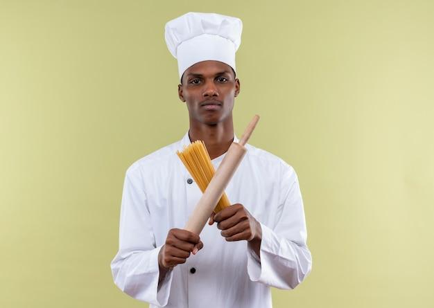 Jeune cuisinier afro-américain confiant en uniforme de chef tient et traverse le rouleau à pâtisserie et tas de spaghettis isolé sur fond vert avec espace copie