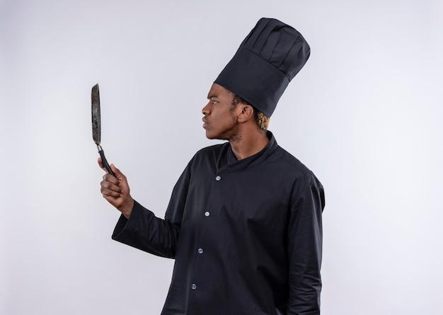 Jeune cuisinier afro-américain confus en uniforme de chef se dresse sur le côté et détient panisolated friture sur mur blanc