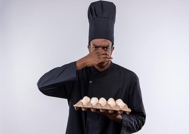 Jeune cuisinier afro-américain ennuyé en uniforme de chef détient lot d'oeufs et ferme le nez avec la main isolé sur fond blanc avec copie espace