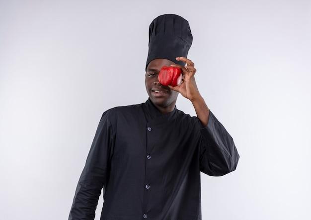 Jeune cuisinier afro-américain heureux en uniforme de chef ferme les yeux avec du poivron rouge sur blanc avec copie espace