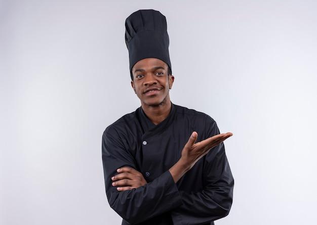 Jeune cuisinier afro-américain souriant en uniforme de chef croise les bras et tient la main ouverte isolé sur mur blanc