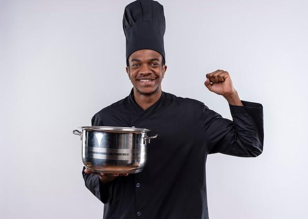 Jeune cuisinier afro-américain souriant en uniforme de chef tient une casserole et lève le poing isolé sur un mur blanc