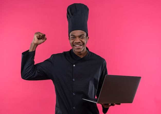 Jeune cuisinier afro-américain souriant en uniforme de chef tient un ordinateur portable et lève le poing isolé sur un mur rose