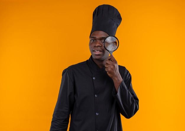 Jeune cuisinier afro-américain surpris en uniforme de chef regarde à travers une loupe sur orange avec copie espace