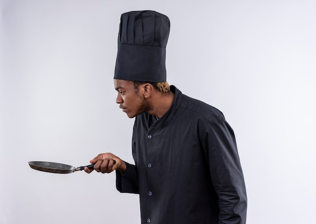 Jeune cuisinier afro-américain surpris en uniforme de chef se tient sur le côté et regarde poêle isolé sur mur blanc