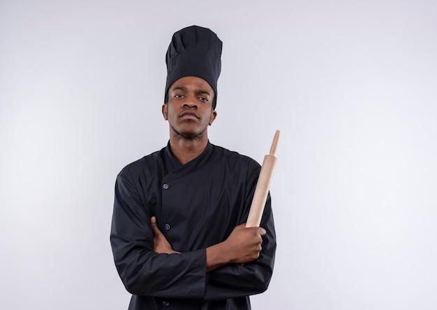 Jeune cuisinier afro-américain en uniforme de chef croise les bras et tient le rouleau à pâtisserie isolé sur fond blanc avec copie espace