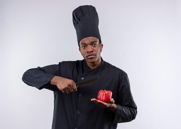 Jeune cuisinier afro-américain en uniforme de chef détient couteau et tomate isolé sur fond blanc avec copie espace