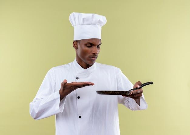 Jeune cuisinier afro-américain en uniforme de chef détient une poêle et des points avec la main isolé sur fond vert avec copie espace