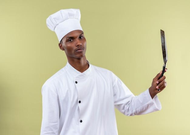 Jeune cuisinier afro-américain en uniforme de chef tient une poêle à frire vers le haut isolé sur fond vert avec copie espace