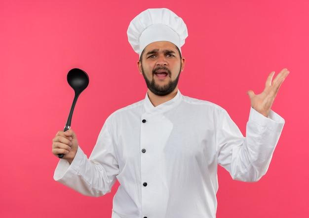 Jeune cuisinier agacé en uniforme de chef tenant une louche et montrant une main vide isolée sur un mur rose