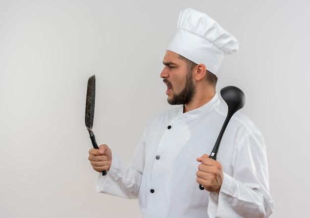 Jeune cuisinier en colère en uniforme de chef tenant une poêle à frire et une louche regardant la poêle isolée sur le mur blanc