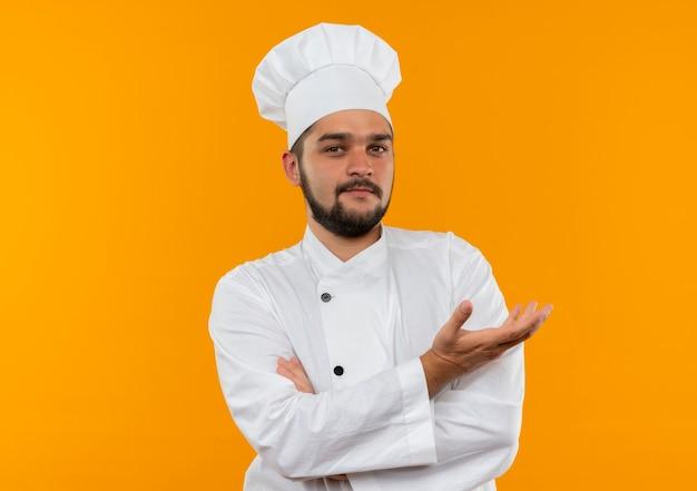 Jeune cuisinier confiant en uniforme de chef debout avec une posture fermée et montrant une main vide isolée sur un mur orange avec espace de copie