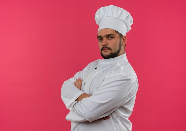 Jeune cuisinier confiant en uniforme de chef debout en vue de profil avec une posture fermée isolée sur un mur rose avec espace de copie