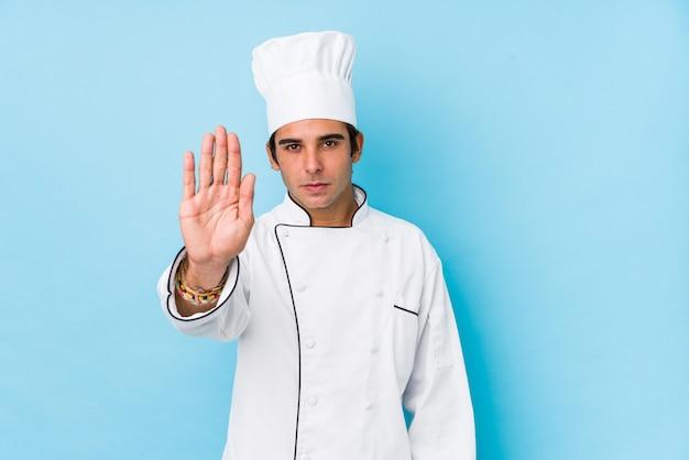 Jeune cuisinier homme isolé debout avec la main tendue montrant le panneau d'arrêt, vous empêchant.