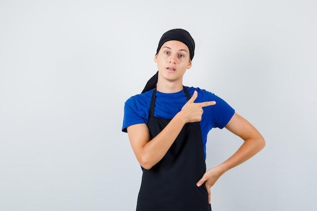 Jeune cuisinier avec la main sur la hanche, pointant vers la droite dans un t-shirt, un tablier et l'air abasourdi. vue de face.