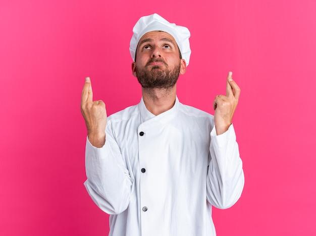 Jeune cuisinier masculin caucasien plein d'espoir en uniforme de chef et casquette en levant faisant un geste de bonne chance isolé sur un mur rose