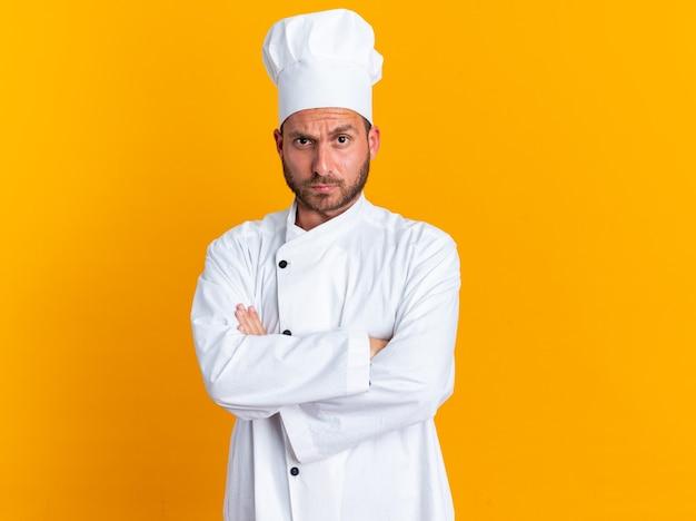 Jeune cuisinier masculin caucasien strict en uniforme de chef et casquette debout avec une posture fermée