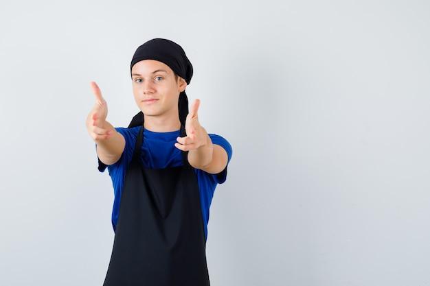 Jeune cuisinier montrant le geste du pistolet en t-shirt, tablier et regardant joyeux, vue de face.