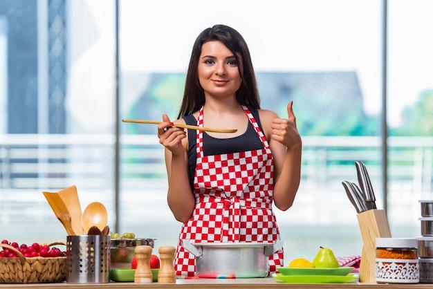 Jeune cuisinier préparant une soupe dans la cuisine