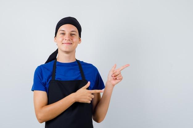 Jeune cuisinier en t-shirt, tablier pointant vers le coin supérieur droit et semblant heureux, vue de face.